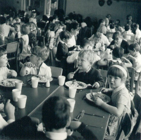 Dinner in the school hall - School dinner - featuring Nicky Carter (with the fork) and Avril Bundell (with the Alice Band), both aged 5. Yvonne Tomlins and Hazel Smoulders are in charge of the table behind.